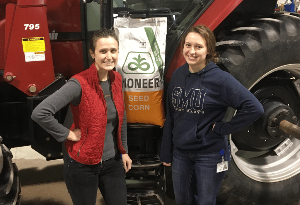 sisters standing in front of tractor