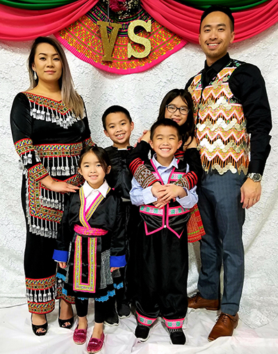 alvin Yang M'17 and his wife, Zong (M'11), pose with their four children while wearing traditional Hmong clothing.