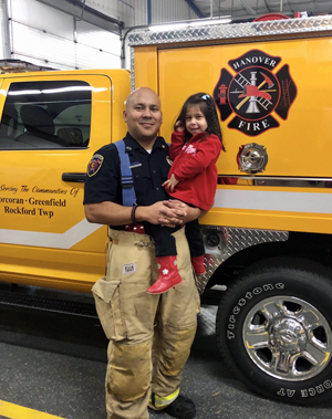 George Diaz stands next to one of the Hanover Fire Department trucks with his daughter, Nora.
