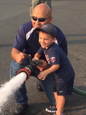 """George Diaz shows his son, Sam, how to use the fire hose. Says Diaz: """"When we're out in the community, the kids will remember that we were at their schools and come talk to us."""""""