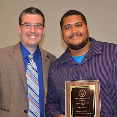 Tim Gossen, vice president for Student Affairs and Student Life, presents Aldontae Guess with the 2019 Student Service Award.