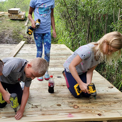 Fourth grader Nate Fuglestad and third grader Avery Olson help construct part of the bridge/boardwalk behind Discovery Middle School. They were just two of the students Lukas Gotto enlisted to help with the project.