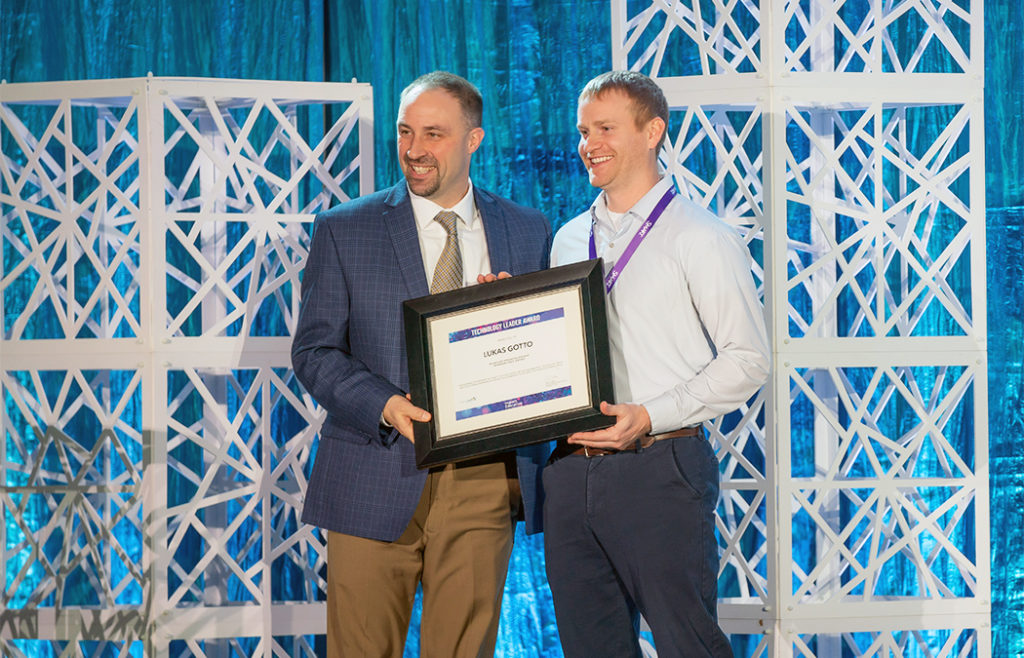 Lukas Gotto stands with Chad Coauette, executive director/CEO of Sourcewell Technology, after being presented with the award.