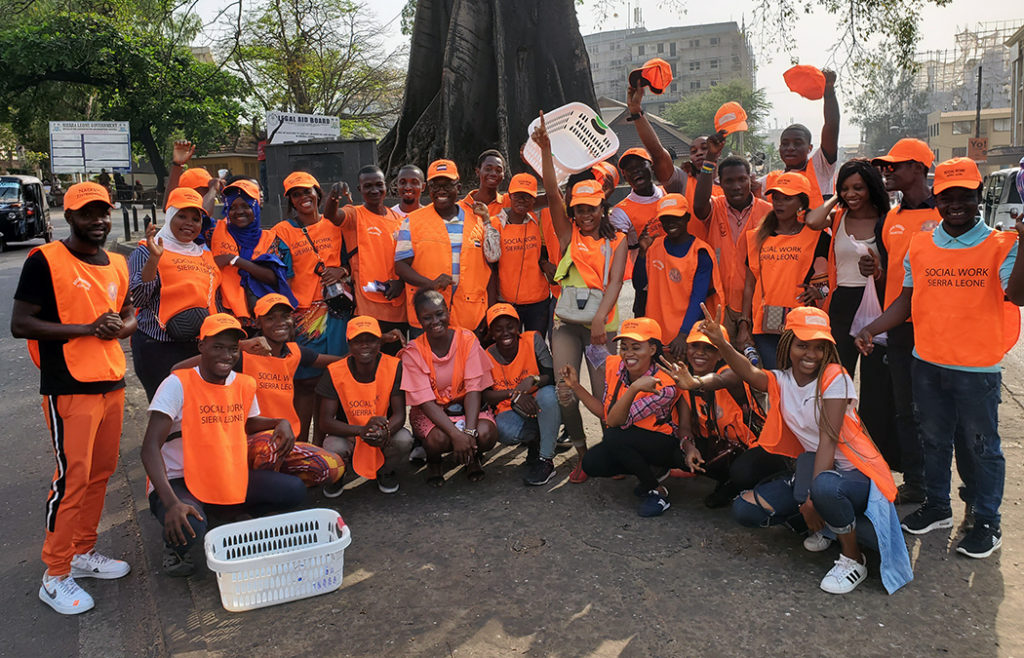 Members of Social Workers Sierra Leone take a group photo clad in their bright orange gifts, which were donated from Sylvester Amara Lamin, associate professor of the MSW program.