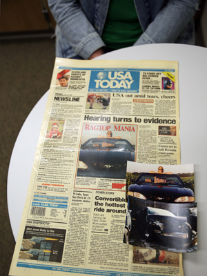Sara Schreiner poses with the front page of USA Today from July 5, 1994, in which she was featured on the front page for a story about the then new Ford Mustang GT. She had just purchased the car after recovering from a serious car accident.