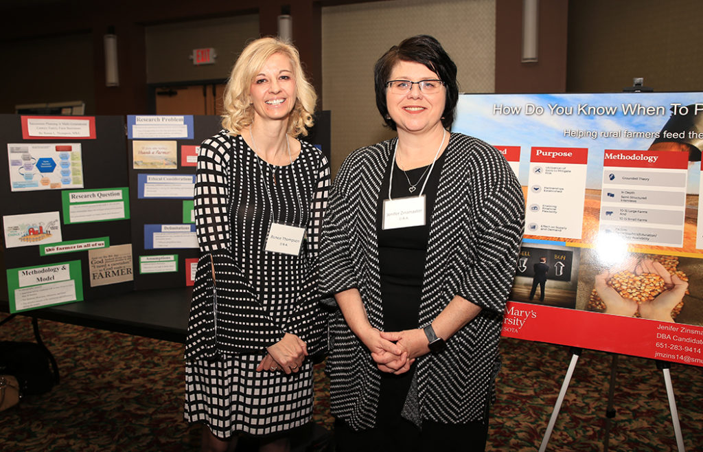 Portrait photo of Renee Thompson and Jenifer Zinsmaster, standing next to their posters at the 16th annual Doctoral Research Symposium on March 7 on the Twin Cities Campus.