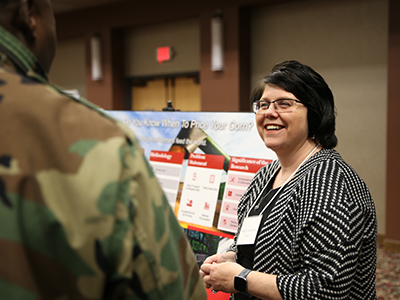 Jenifer Zinsmaster speaks with someone about her research at the 16th annual Doctoral Research Symposium on March 7.