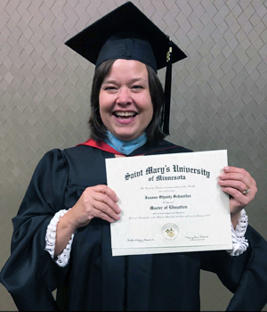 This a photo of Joanne Schneider with her diploma during her commencement ceremony.