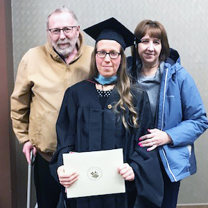 This is a photo of Amanda Otero with her parents, Ron and Tami Bakeberg, during her graduation ceremony at Saint Mary's.